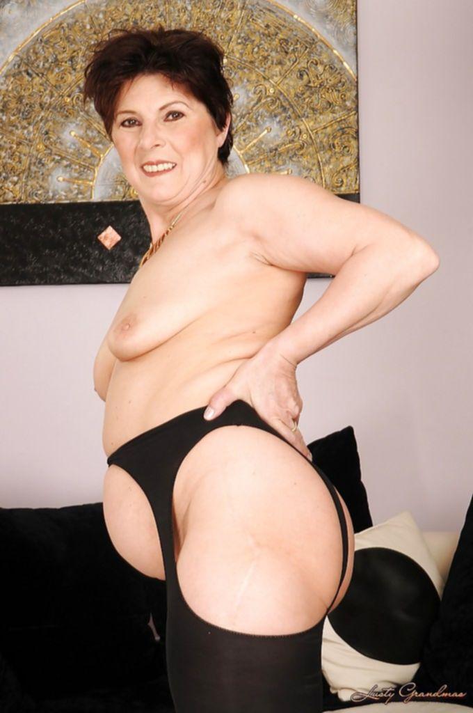 Бабуля в чулках и с небритой мандой раздевается возле дивана - секс порно фото