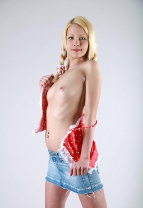 Молодая блондинка сидит, раздвинув ноги на белой кровати - секс порно фото