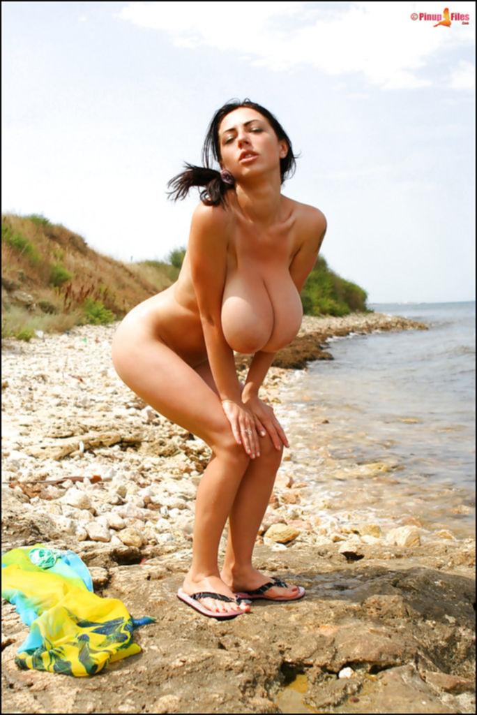 Грудастая деваха позирует на берегу моря - секс порно фото