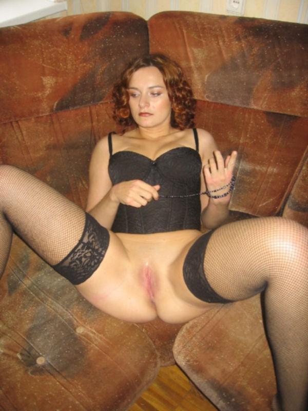 Рыжая баба в чулках с корсетом и чокером на шее шалит на диване - секс порно фото