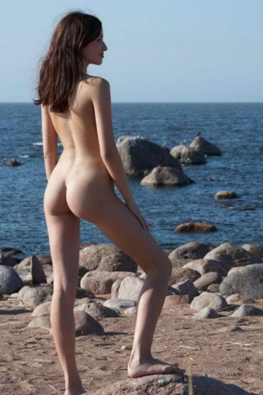Молодая брюнетка позирует на песке у моря без одежды - секс порно фото