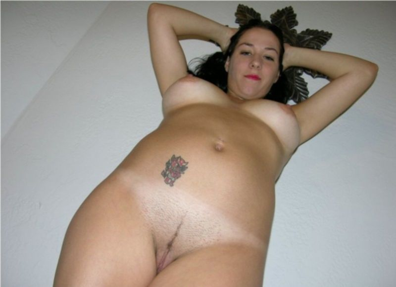 Брюнетка с татуировкой на животе разлеглась на кровати - секс порно фото