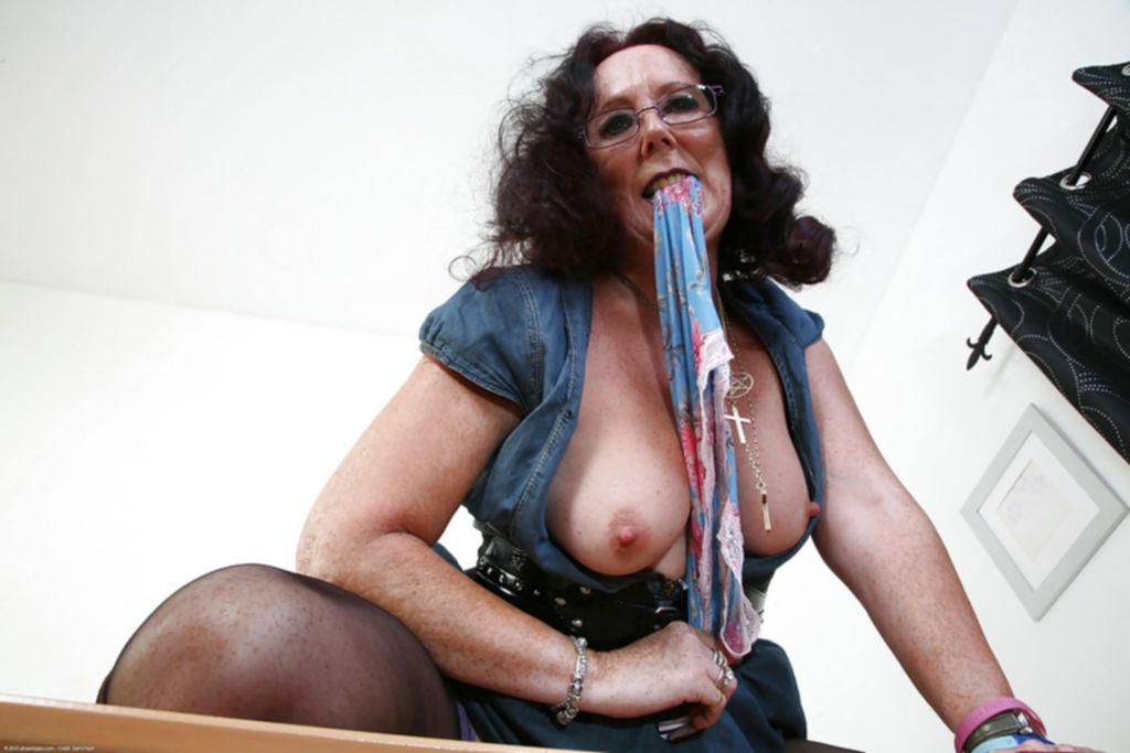 Похотливая бабка в сапогах светит большой попой и киской на столе - секс порно фото