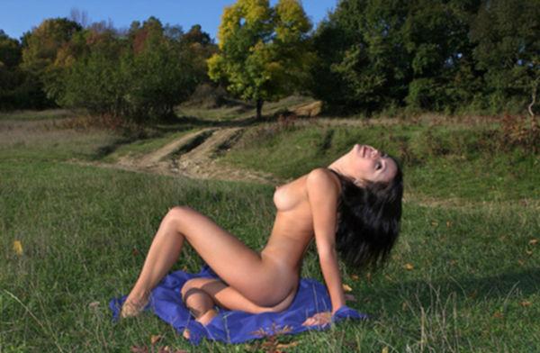 Сисястая брюнетка позирует голая на синем покрывале и у дерева - секс порно фото